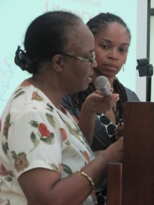 Poet Ann-Margaret Lim holds the microphone for Jean Goulbourne, who read at today's celebration of International Literacy Day at the Ministry of Foreign Affairs and Foreign Trade. (My photo)