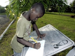 Akeem Williams, a nine-year-old student of Clan Carty Primary School in Kingston, is busy taking notes on Jamaica's national heroes during the Salute to Heroes at the National Heroes Park in 2010. (Photo: Norman Grindley/Gleaner).