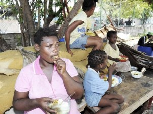 Novia Beckford sits on her bed having a meal with three of her children after their house was demolished on Duke Street in August 2012. (Photo: Norman Grindley/Gleaner)
