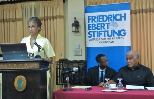 Judith Wedderburn of Friedrich Ebert Stiftung welcomes participants to the National Consultations on Climate Change on November 6. Seated are (left) Dr. Orville Grey, Senior Technical Officer in the Climate Change Division; and Minister of Water Land Environment and Climate Change Hon. Robert Pickersgill.