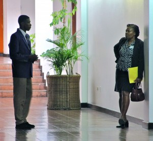 A student discusses his presentation with his teacher/advisor before going before the panel of judges at the Junior Achievement Jamaica meeting on November 18. (My photo)