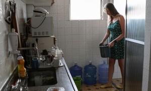 Isabela Berger Sacramento tops up her water stocks. Photograph: Juliana Spinola/Demotix