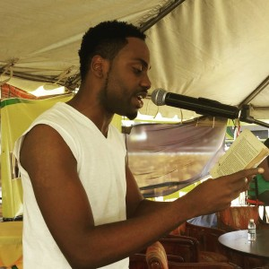 """Akeem Mignott reads from Vic Reid's """"New Day."""" (Photo: Facebook)"""