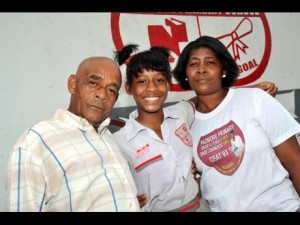 Moving up: Danielle Dunbar (centre) poses with her parents, Conrad and Marlene Dunbar, after the Padmore Primary School student received her Grade Six Achievement Test results this year. Danielle is now attending Campion High School. (Photo: Norman Grindley/Gleaner)