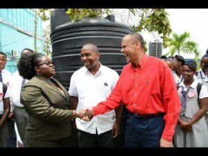 The private sector has played its part in donating water tanks to schools. Here, the President of Gaurdian Life presents a water tank to Hazel Cameron principal of Clan Carthy High School while Julian Robinson(centre) and students look on. Guardian Life Limited has donated a total of 15 1000-gallon water tanks to 15 schools in Kingston and St Andrew to ease water storage during times of drought. Digicel and other firms have also donated water tanks. (Photo: Gleaner)