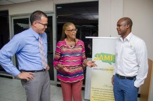 Chief Technical Director in the Ministry of Finance and Planning's Financial Investigation Division (FID), Robin Sykes, talking to Chair of the Jamaica Association for Micro Financing (JAMFIN), Dr. Blossom O'Meally-Nelson; and Branditise.com Chief Executive Officer, Wayne Marsh at JAMFIN's quarterly meeting in July. (Photo: Jamaica Information Service)