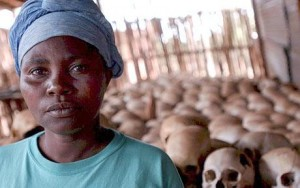 A survivor of the Rwandan genocide with skulls in the background. (Photo: EPA)