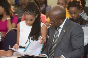 """MC Saneta Myrie goes over the program with guest speaker and State Minister in the Ministry of National Security Pearnel Charles Jr., who stressed that """"unprecedented levels of collaboration"""" are needed to tackle adolescent HIV and AIDS. (Photo: JYAN/Facebook)"""