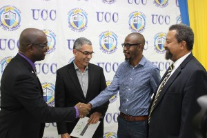 This should be a great partnership: Group Executive Chairman of UCC Dr. Winston Adams (left) shakes hands with Tyrone Wilson, while eMedia Interactive Group Chair Richard Byles (2nd left) and Executive Chancellor of UCC Professor Dennis Gayle look on. (Photo: UCC/Facebook)