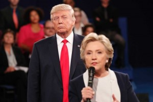 I'm going to lock you up… Donald Trump glowers in the background as Hillary Clinton speaks at the second debate. (Photo: Reuters)