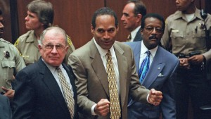 O.J. Simpson, center, reacts as he is found not guilty of killing his ex-wife Nicole Brown and her friend Ron Goldman, as members of his defense team, F. Lee Bailey, left, and Johnnie Cochran Jr., right, look on, in court in Los Angeles on Oct. 3, 1995. (Myung J. Chun / Associated Press)