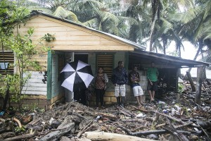 A home is surrounded by debris brought in by Hurricane Irma in Nagua, Dominican Republic, Thursday, Sept. 7, 2017. Irma flooded parts of the Dominican Republic when it roared by Thursday, just off the northern coast of the island it shares with Haiti. (AP Photo/Tatiana Fernandez)