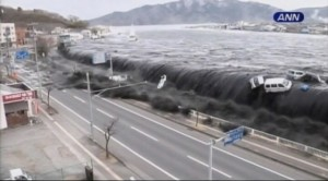 A still from footage of a tsunami in Japan, about to overwhelm a town.
