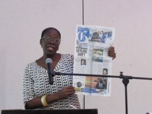 "Vice President of the GTNA Edith Williams holds up the front page of the Jamaica Gleaner: ""Skyline Shift."" (My photo)"